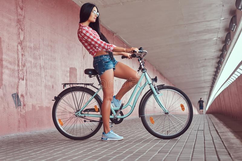stylish brunette girl wearing a pink flannel shirt and denim shorts in glasses, posing with city bike against a royalty free stock photography