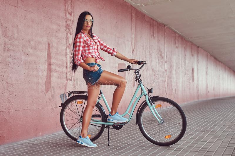 stylish brunette girl wearing a pink flannel shirt and denim shorts in glasses, posing with city bike against a royalty free stock photos