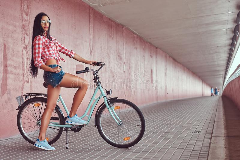 stylish brunette girl wearing a pink flannel shirt and denim shorts in glasses, posing with city bike against a stock photos