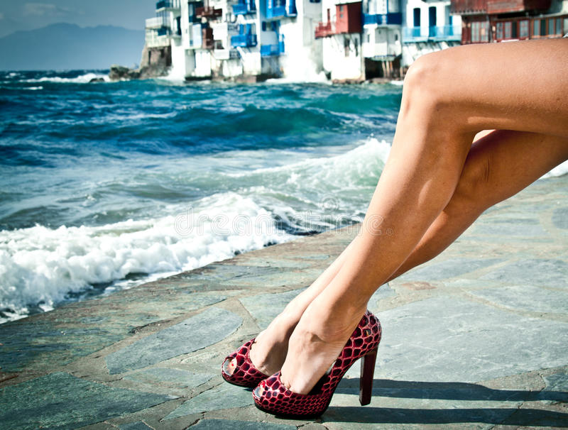 Summer legs by the sea. Summer legs in high heels by the sea in Mykonos, Greece royalty free stock photo