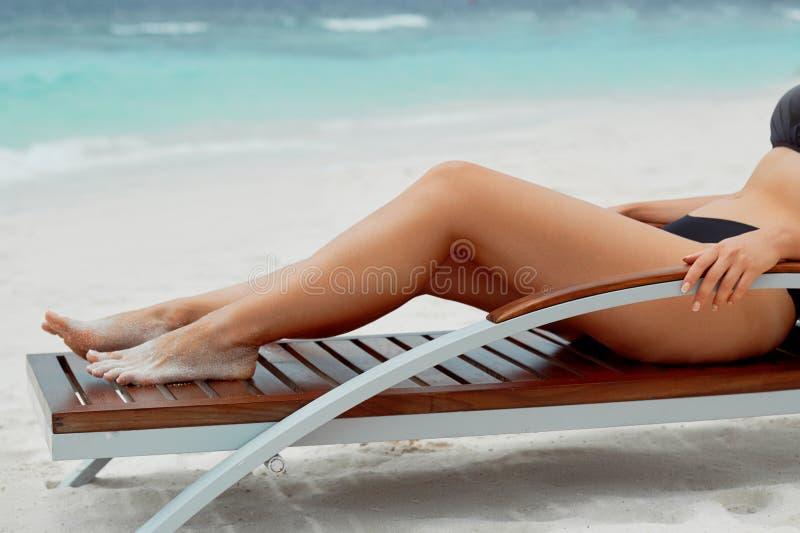 Sexy Suntan Bikin Woman Legs Relaxing Lying Down near Beach In Resort Spa Hotel On Travel Holidays Vacation. Beauty Skincare. Protection Sun. Epilation Laser stock photography