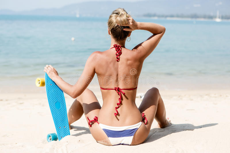 suntanned lady with the blue penny board rests on the beach stock image