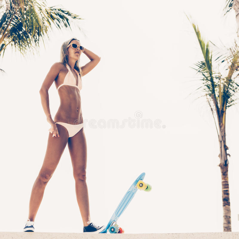 suntanned lady is ready to go on penny board royalty free stock photography