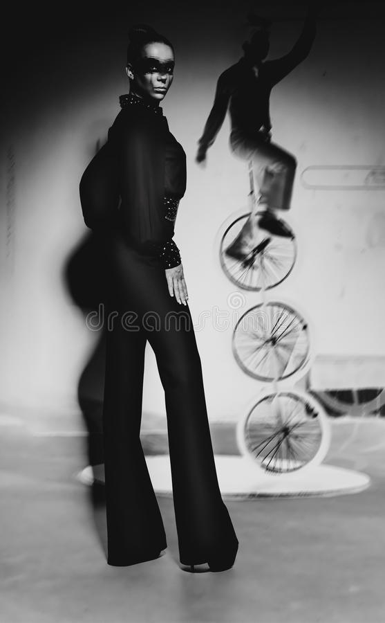 Tall woman in black pants. In dark stock photography