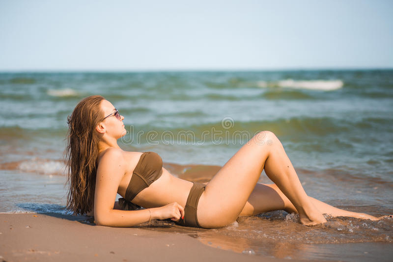 tanned girl in a bathing suit lies on the seashore royalty free stock photos