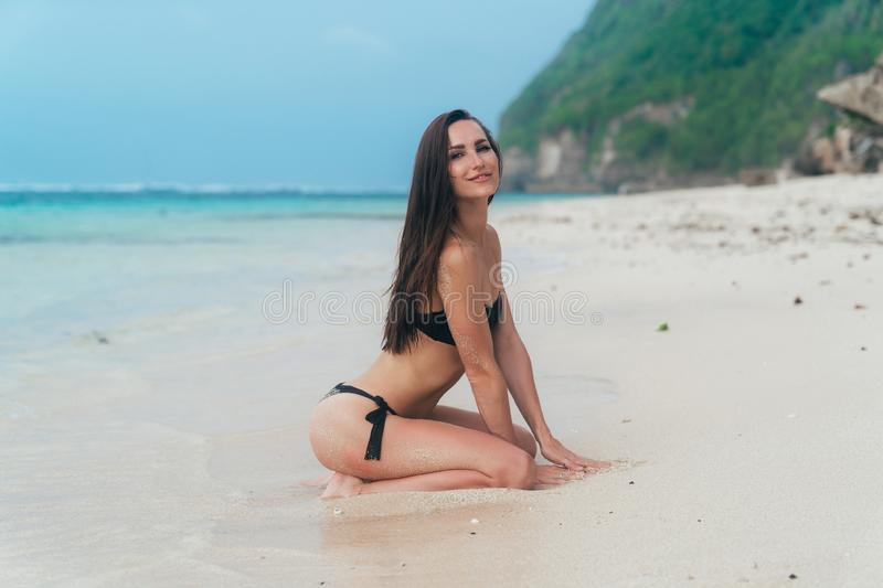 Sexy tanned girl in black swimsuit posing on sandy beach near ocean. Beautiful model sunbathes and rests royalty free stock photo