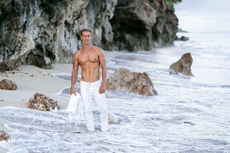 Sexy tanned man in white pants walks on beach with ocean waves at background royalty free stock images