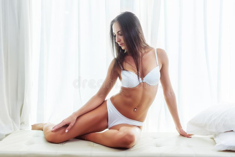 tanned young brunette female model in underwear sitting posing in white interior with curtains in the background. stock images