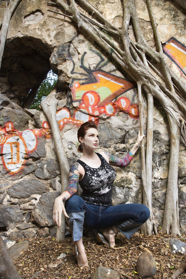 Tattooed woman. Caucasian tattooed woman crouching next to wall covered in graffiti and Banyan tree branches royalty free stock images