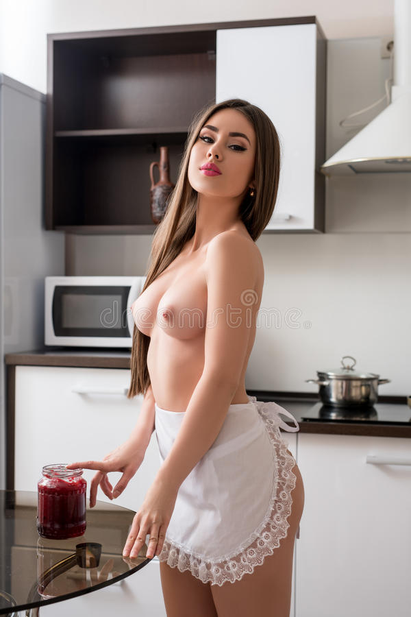 topless model wearing maid's apron in kitchen stock image - image of