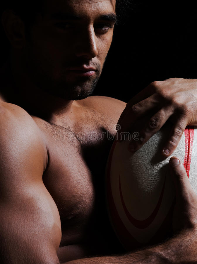Topless rugby man portrait. One caucasian topless man portrait hugging a rugby ball on studio black background stock image