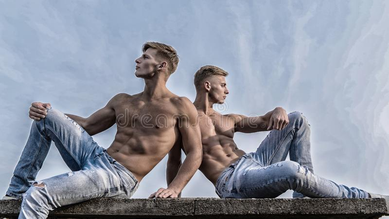 Sexy torso attractive body. Denim pants emphasize masculinity sexuality. Men twins brothers muscular guys sit relax sky. Background. Men strong muscular athlete stock photos