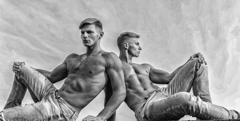 Sexy torso attractive body. Denim pants emphasize masculinity sexuality. Men twins brothers muscular guys sit relax sky. Background. Men strong muscular athlete royalty free stock photos