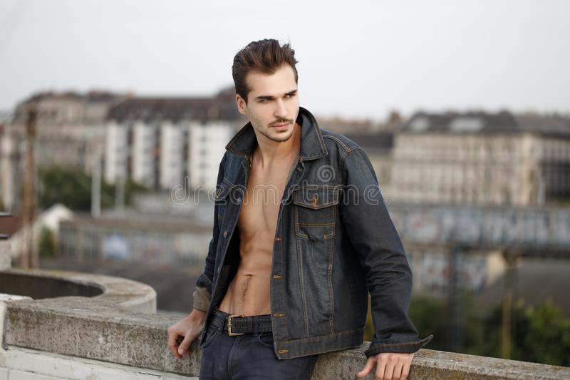 Trendy man in denim posing outdoors in city. Trendy muscular man with abs in denim posing outdoors in city stock photos