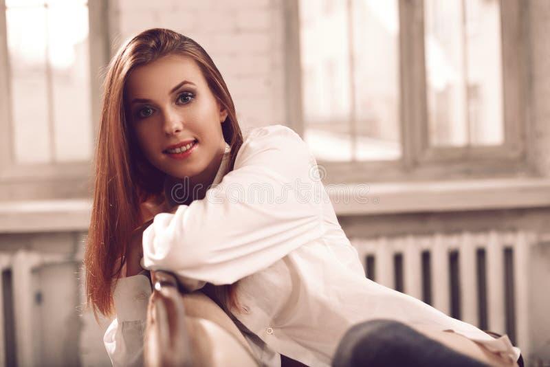 Sexy und attraktive junge Frau mit dem langen Haar, das auf Sofa im BH sitzt stockfotografie
