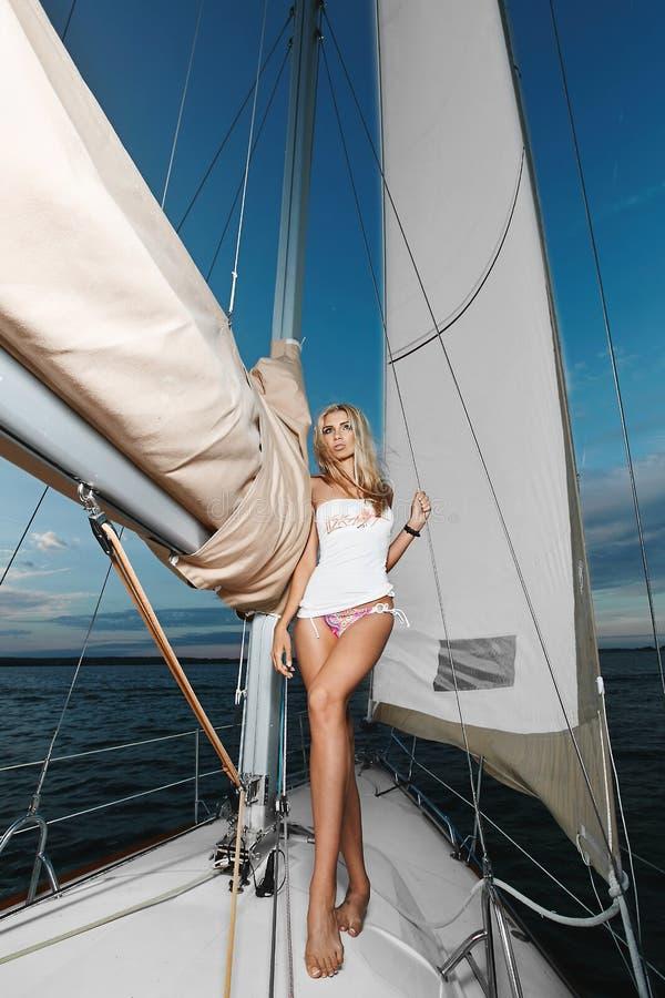 Sexy und fasionable langbeiniges blondes vorbildliches Mädchen mit perfektem Körper im Bikini und in weißem T-Shirt, die nahe Ste stockbild