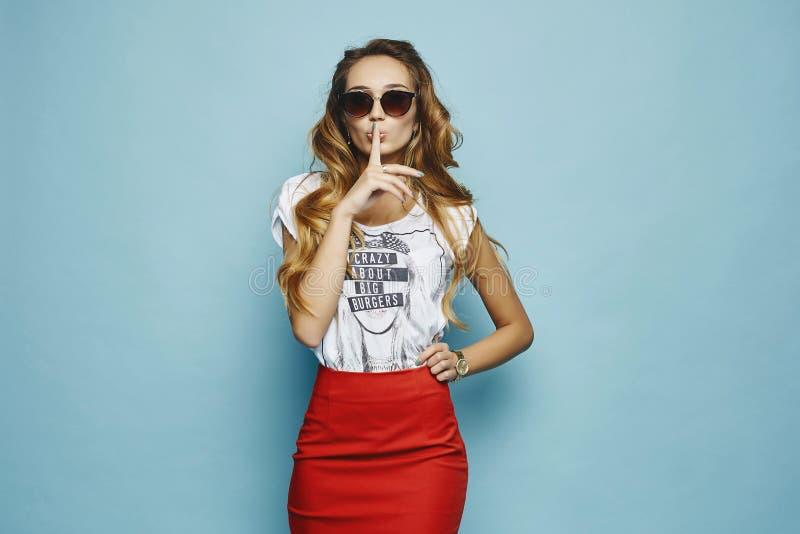 Sexy und modernes blondes vorbildliches Mädchen mit Berufsmake-up und stilvoller Sonnenbrille im roten Rock und im weißen T-Shirt lizenzfreies stockfoto