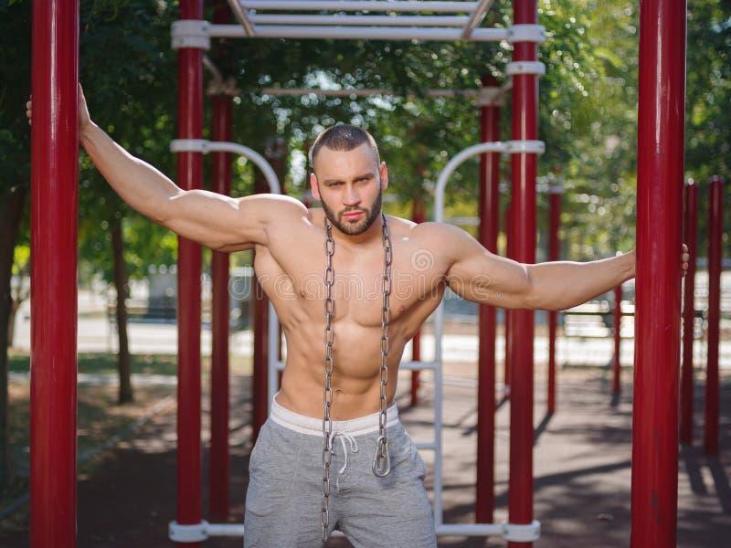 Sexy und muskulöser hemdloser Bodybuildermann, der auf einem unscharfen Hintergrund vorführt Ausarbeiten des Konzeptes stockbilder