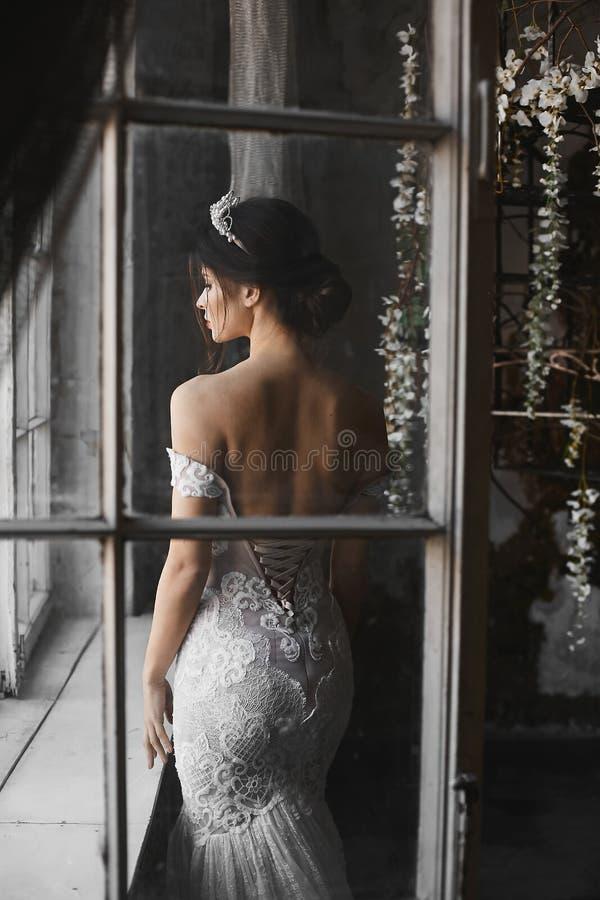 Sexy und schönes Brunettemodellmädchen im weißen Kleid der Spitzes mit nackten Schultern mit Diadem auf ihrem Kopf steht nahe dem stockbild