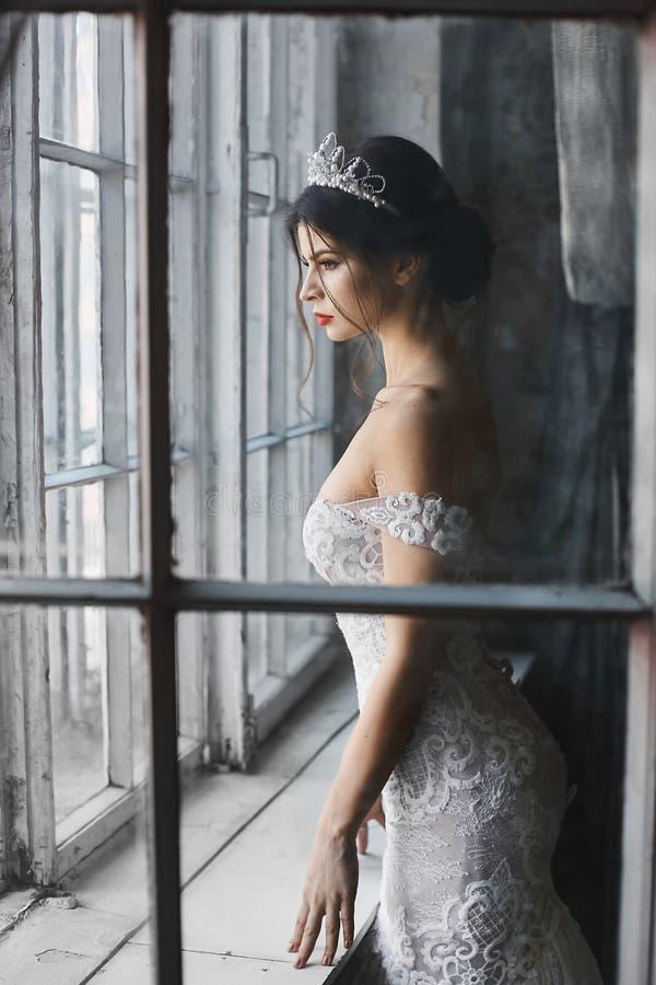 Sexy und schönes Brunettemodellmädchen im weißen Kleid der Spitzes mit nackten Schultern und in einem Diadem auf ihrem Kopf steht lizenzfreies stockbild