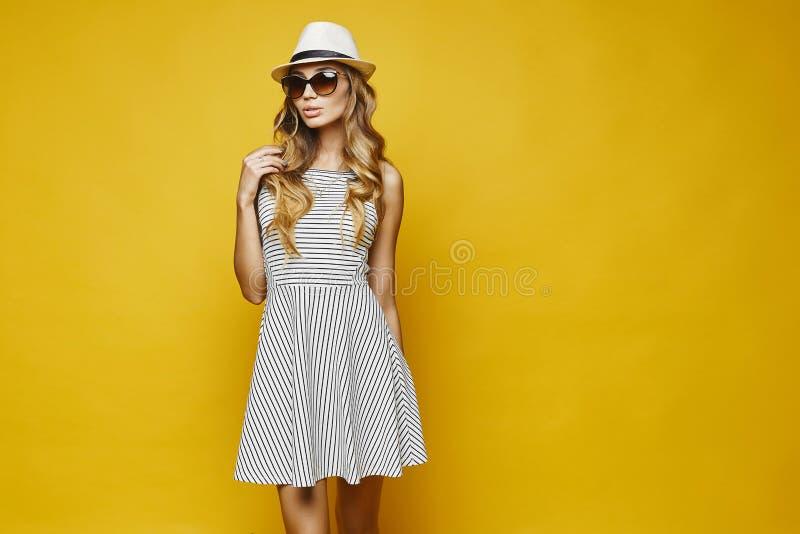 Sexy und sinnliche blonde vorbildliche junge Frau mit den sexy Lippen, im Weiß streifte das Kleid, Hut und Sonnenbrille und justi stockfotos