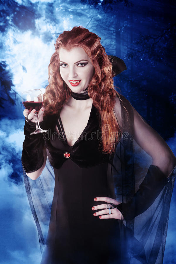 Vampire girl with glass of blood in the woods at night. Vampire girl with glass of blood in scary woods at night stock images