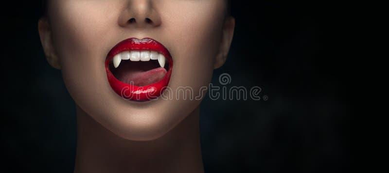 Sexy Vampire Woman's roten blutigen Lippen in der Nähe Vampire Girl leckt Fangzähne mit Zunge Fashion Glamour Halloween Kunstdesi stockfotografie