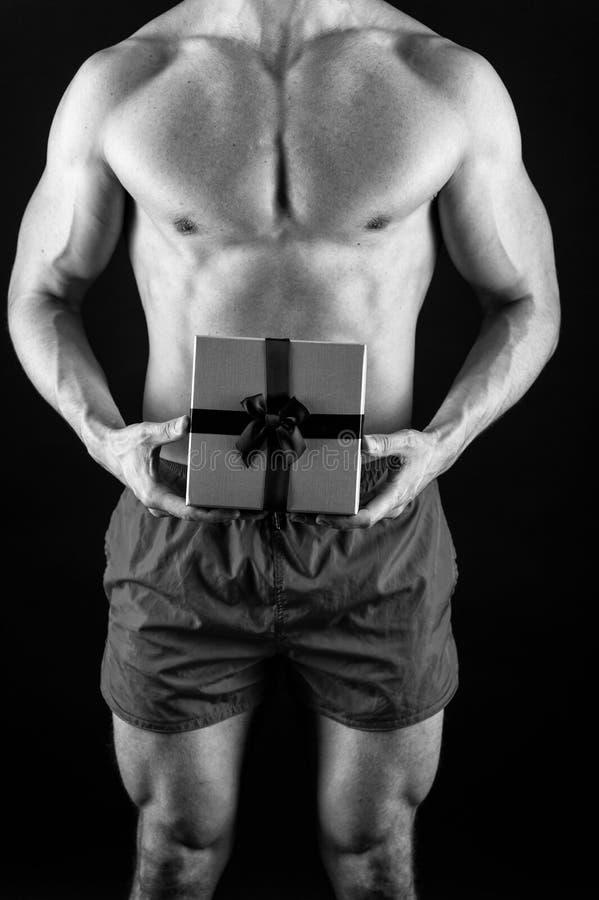 Sexy verrassingsconcept Macho het spiertorso stellen met giftdoos De Kerstman voor volwassen meisjes Sexy atletische macho stock foto's