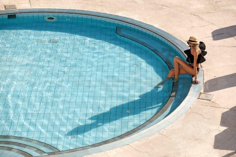 Sexy vrouw in bikini die de zomer van zon genieten en tijdens vakantie dichtbij de pool looien stock afbeeldingen