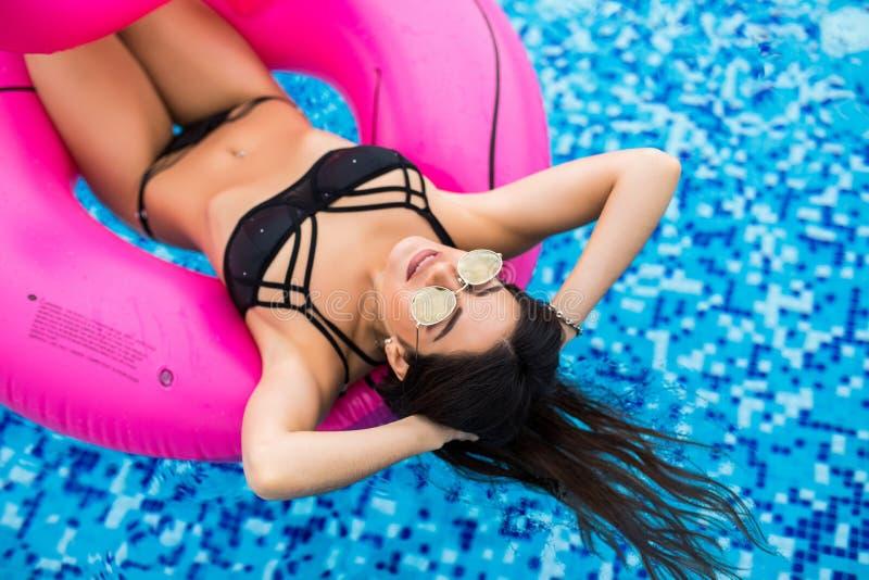 Sexy vrouw in bikini die de zomer van zon genieten en tijdens vakantie in pool met cocktail looien Hoogste mening Vrouw in zwemba stock foto's