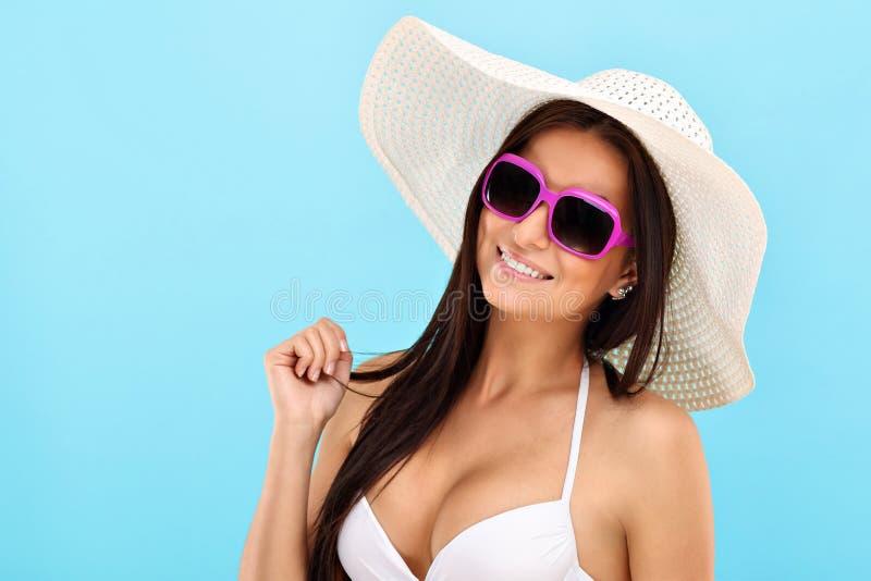 Sexy vrouw in bikini het stellen tegen blauwe achtergrond stock afbeelding