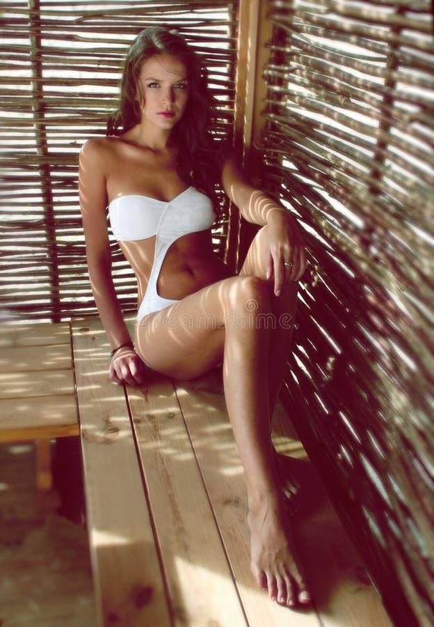 Sexy vrouw in de witte zitting van het ontwerperzwempak in een strandgazebo stock foto