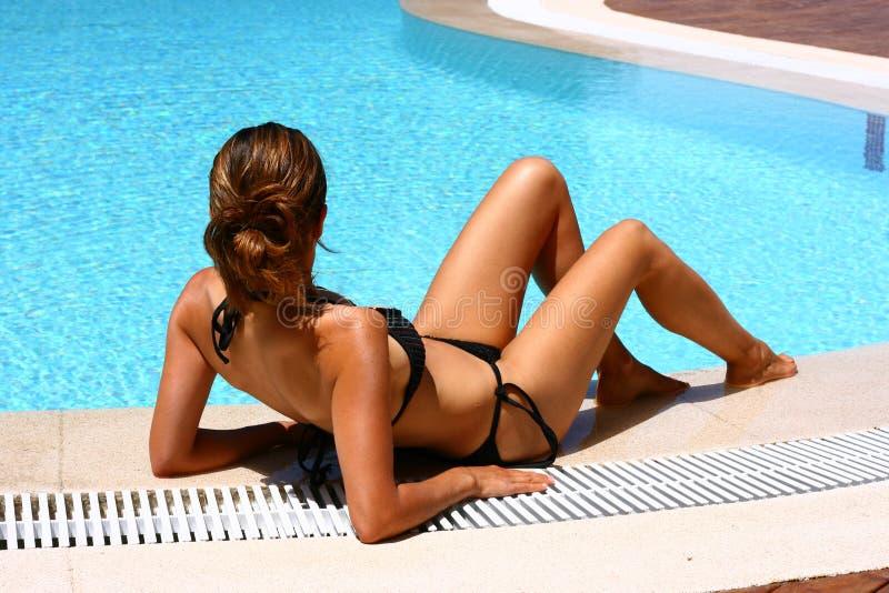 Sexy Vrouw die bij de pool legt stock foto