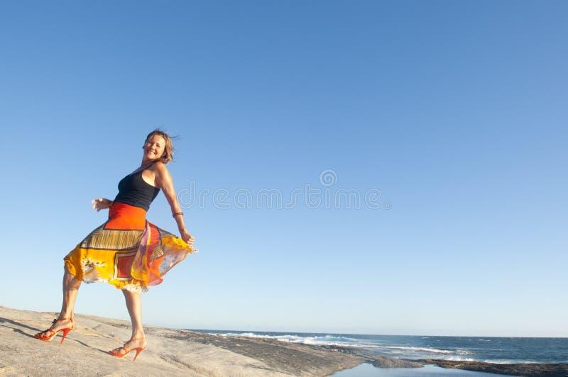 Sexy vrouw die bij kust danst stock afbeeldingen