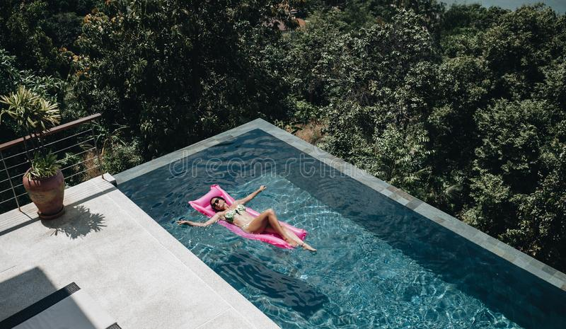 Sexy vrouw die in bikini de zomer van zon in zwembad genieten stock foto's