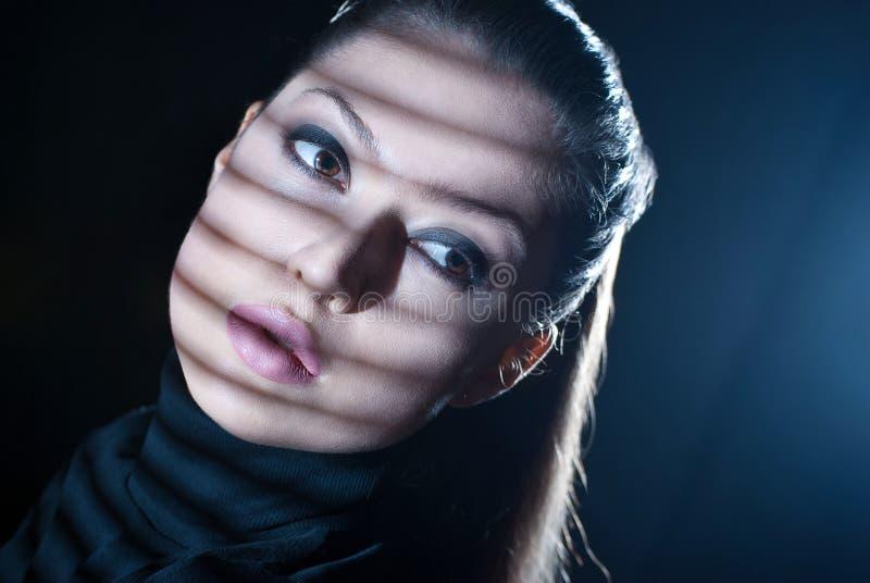 Sexy vrouw die door venster met jaloezie kijken stock foto's