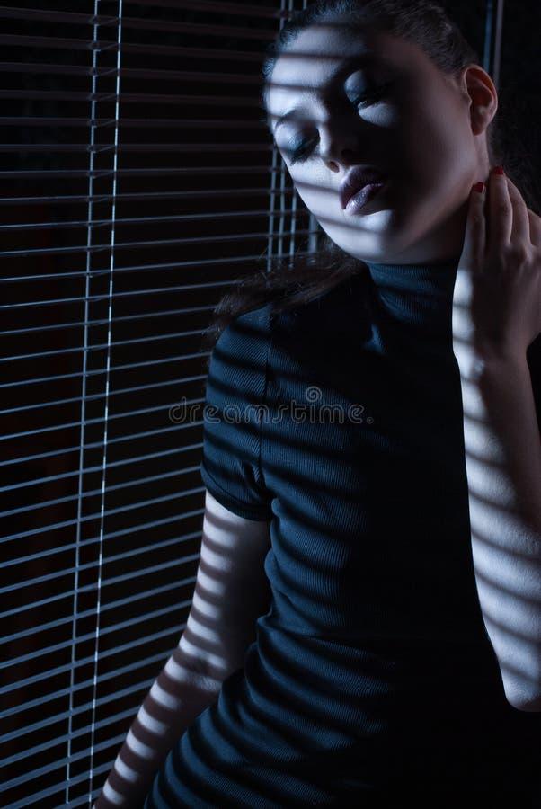 Sexy vrouw die door venster met jaloezie kijken stock fotografie