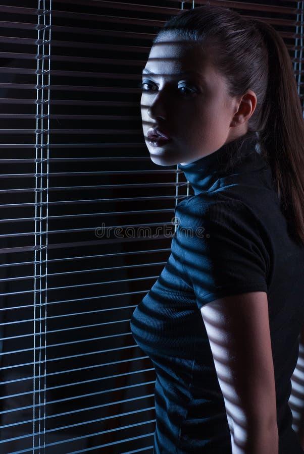 Sexy vrouw die door venster met jaloezie kijken royalty-vrije stock afbeeldingen