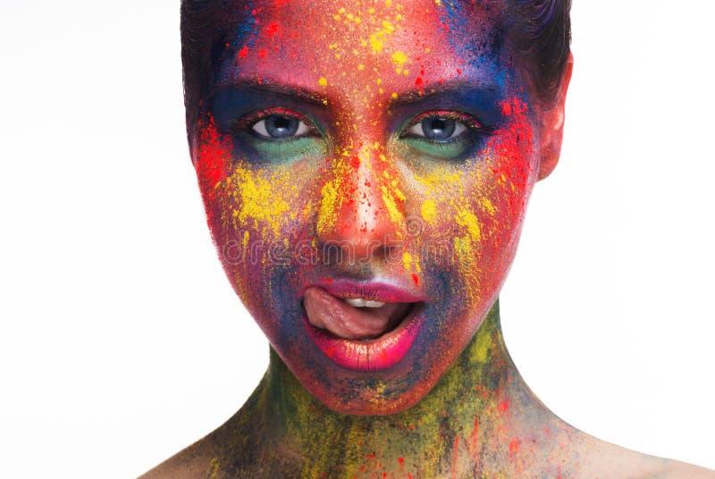Sexy vrouw die met heldere creatieve make-up haar lippen likken stock foto