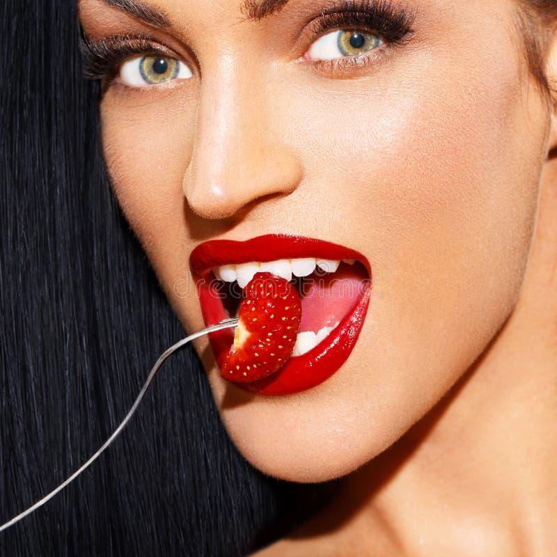 Sexy vrouw die met rode lippen aardbei eten stock afbeelding