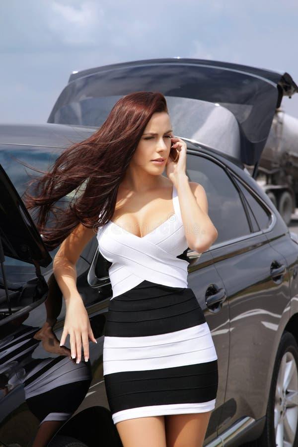 Sexy vrouw die zich dichtbij gebroken auto bevinden om de hulpdiensten te roepen stock foto's