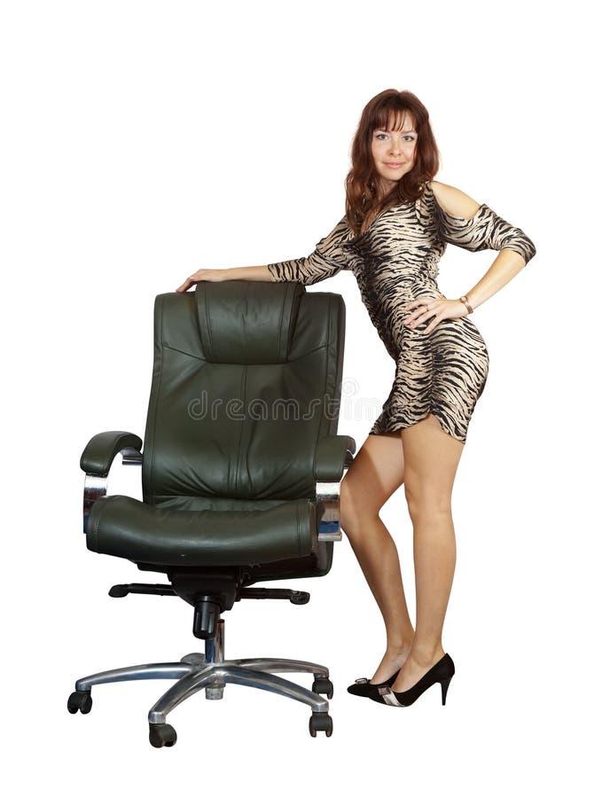 Sexy vrouw die zich met bureauleunstoel bevindt stock afbeeldingen
