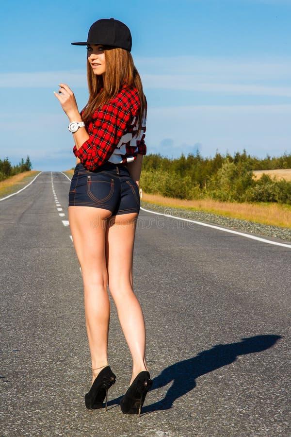 Sexy vrouw in een gecontroleerd overhemd op de weg royalty-vrije stock afbeelding