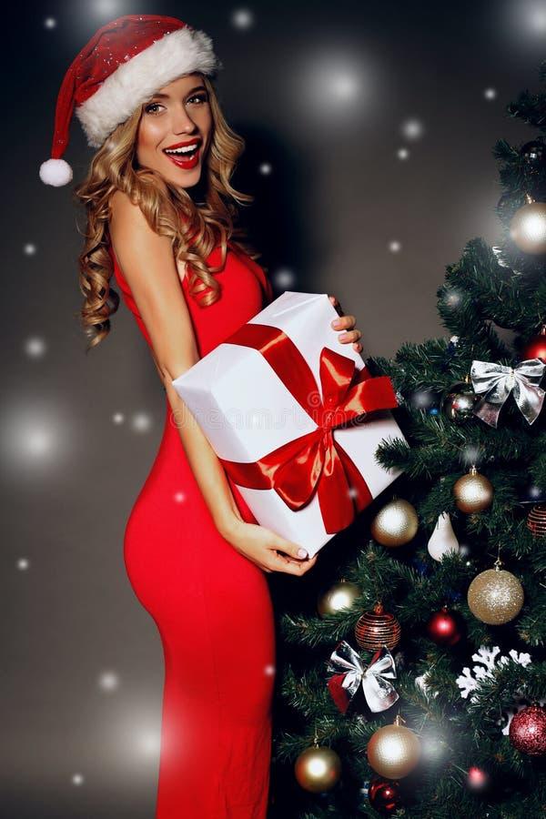 Sexy vrouw in een rode Kerstmanhoed die gift-dozen houden dichtbij Kerstboom stock foto