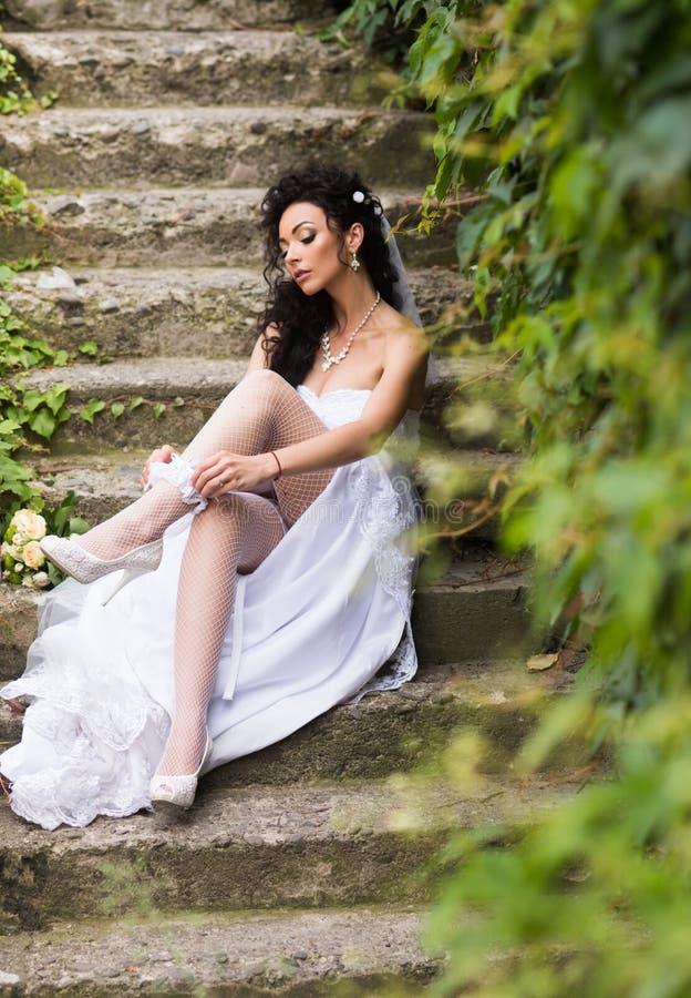 Sexy vrouw in kousenlingerie op huwelijksdag Het kantkouseband van de vrouwenslijtage op been Meisje met bruids make-up en kapsel stock foto