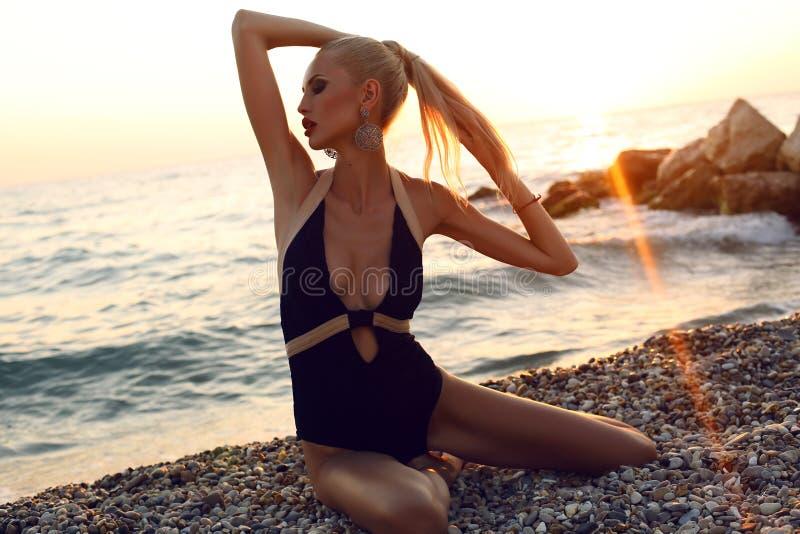 Sexy vrouw met blond haar in zwempak het stellen op strand stock fotografie