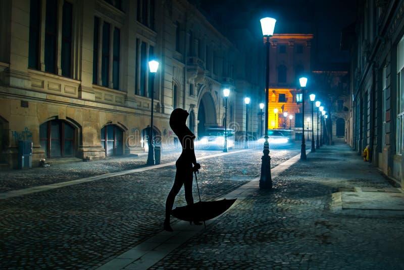 Sexy Vrouw met paraplu alleen in de straat bij nacht die alleen in regen lopen stock fotografie