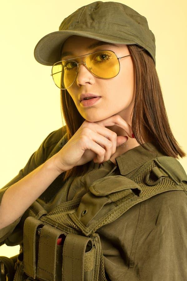 Sexy vrouw in militair` s kostuum op gele achtergrond royalty-vrije stock afbeeldingen