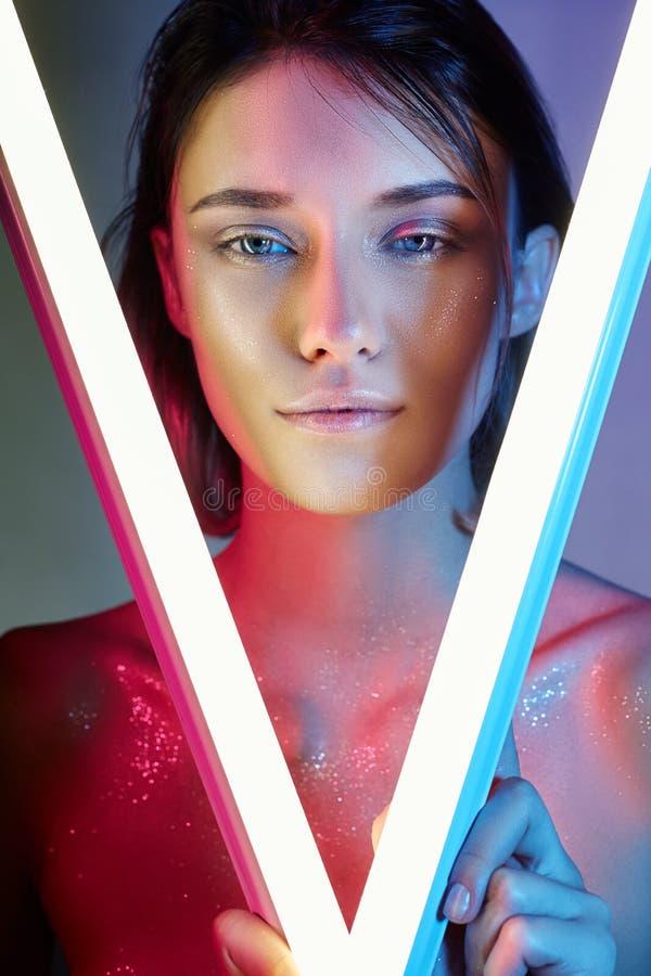Sexy vrouw in neonlicht in lingerie Neonlichten en glans van licht op het meisjesgezicht Naakte vrouw in lovertjes op de achtergr royalty-vrije stock fotografie