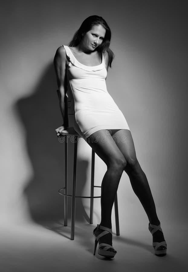 Sexy vrouw op de hoge stoel royalty-vrije stock afbeelding